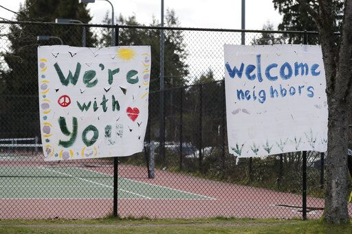 In this photo taken Tuesday, March 24, 2020, handmade signs posted to a tennis court fence are set to greet future patients at a temporary field hospital for coronavirus patients on an adjacent soccer field in the Seattle suburb of Shoreline, Wash. With U.S. hospital capacity stretched thin, hospitals around the country are scrambling to find space for a coming flood of COVID-19 patients, opening older closed hospitals and repurposing other buildings.