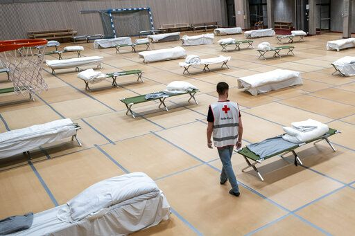 A Red Cross volunteer looks at beds set up for homeless people in the gymnasium of Uranienborg school, which is closed due to the corona eruption, in Oslo, Thursday, March 26, 2020. The new coronavirus causes mild or moderate symptoms for most people, but for some, especially older adults and people with existing health problems, it can cause more severe illness or death. (Heiko Junge/NTB Scanpix via AP)