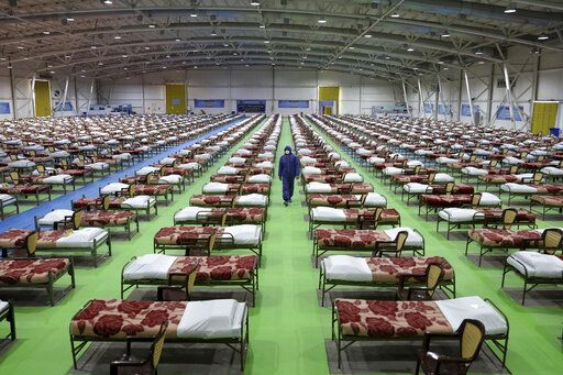 A member of the Iranian army walks past rows of beds at a temporary 2,000-bed hospital for COVID-19 coronavirus patients set up by the army at the international exhibition center in northern Tehran, Iran, on Thursday, March 26, 2020.