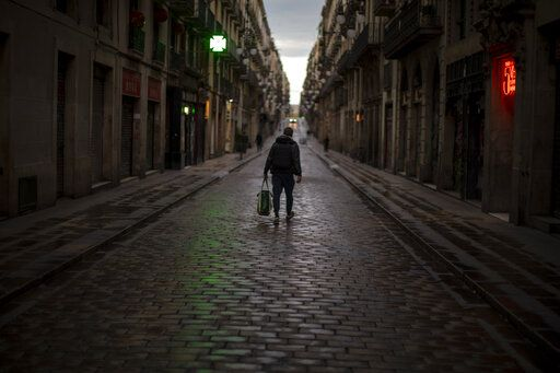 A man walks along an empty street in downtown Barcelona, Spain, Thursday, March 26, 2020 as the lockdown to combat the spread of coronavirus continues. The new coronavirus causes mild or moderate symptoms for most people, but for some, especially older adults and people with existing health problems, it can cause more severe illness or death.