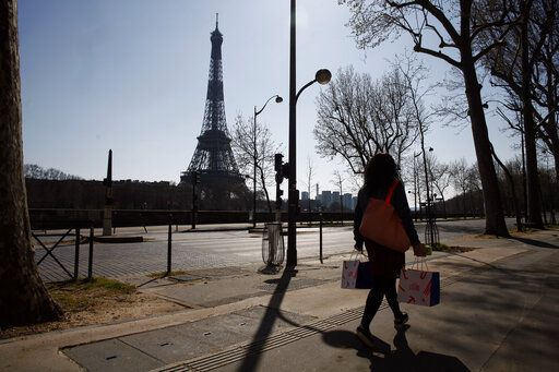 A woman walks in an empty street near the Eiffel Tower during a nationwide confinement to counter the new coronavirus, in Paris, Thursday, March 26, 2020. The new coronavirus causes mild or moderate symptoms for most people, but for some, especially older adults and people with existing health problems, it can cause more severe illness or death.