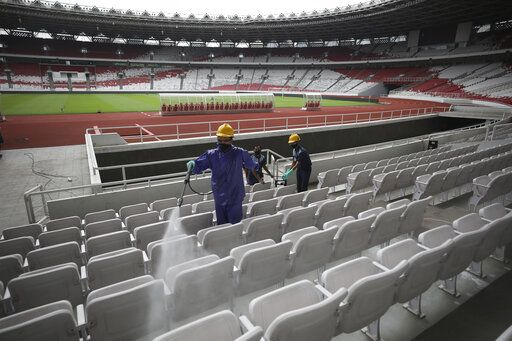 Workers spray disinfectant over spectator seats at the Gelora Bung Karno Main Stadium in efforts to curb the spread of the coronavirus outbreak, in Jakarta, Indonesia, Thursday, March 26, 2020. The new coronavirus causes mild or moderate symptoms for most people, but for some, especially older adults and people with existing health problems, it can cause more severe illness or death.