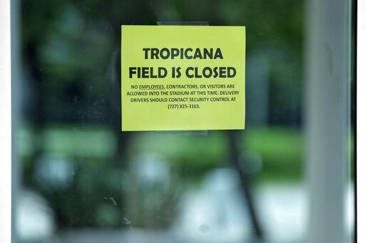 A closed sign is posted on the door at Tropicana Field, the home of the Tampa Bay Rays, Thursday, March 26, 2020, in St. Petersburg, Fla. Major League Baseball's regular season has been delayed in an attempt to help stop the spread of the coronavirus. The Rays were scheduled to open the season against the Pittsburgh Pirates.