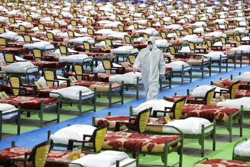 A person in protective clothing walks through a temporary 2,000-bed hospital for COVID-19 coronavirus patients set up by the Iranian army at the international exhibition center in northern Tehran, Iran, on Thursday, March 26, 2020.