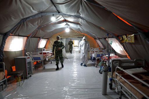 Iranian army soldiers work in a temporary 2,000-bed hospital for COVID-19 coronavirus patients set up by the army at the international exhibition center in northern Tehran, Iran, on Thursday, March 26, 2020.