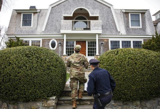 Rhode Island Air National Guard Tsgt. William Randall, left, and Westerly police officer Howard Mills approach a home while looking for New York license plates in driveways to inform them of self quarantine orders, Saturday, March 28, 2020, in Westerly, R.I. States are pulling back the welcome mat for travelers from the New York area, which is the epicenter of the country's coronavirus outbreak, and some say at least one state's measures are unconstitutional. Gov. Gina Raimondo ratcheted up the measures announcing she ordered the state National Guard to go door-to-door in coastal communities starting this weekend to find out whether any of the home's residents have recently arrived from New York and inform them of the quarantine order.