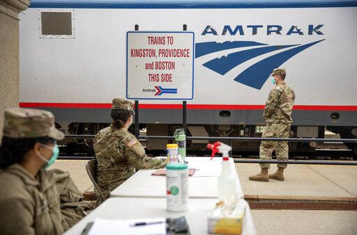 Members of the Rhode Island National Guard look for passengers getting off a train from New York as it arrives Saturday, March 28, 2020, in Westerly, R.I. States are pulling back the welcome mat for travelers from the New York area, which is the epicenter of the country's coronavirus outbreak, and some say at least one state's measures are unconstitutional. Gov. Gina Raimondo ratcheted up the measures announcing she'll also order the state National Guard to go door-to-door in coastal communities starting this weekend to find out whether any of the home's residents have recently arrived from New York and inform them of the quarantine order.