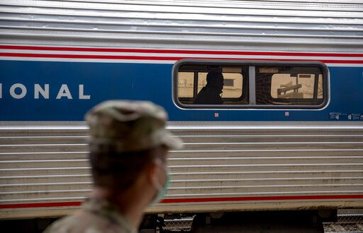A soldier with the Rhode Island National Guard looks for passengers getting off a train from New York as it arrives Saturday, March 28, 2020, in Westerly, R.I. States are pulling back the welcome mat for travelers from the New York area, which is the epicenter of the country's coronavirus outbreak, and some say at least one state's measures are unconstitutional. Gov. Gina Raimondo ratcheted up the measures announcing she'll also order the state National Guard to go door-to-door in coastal communities starting this weekend to find out whether any of the home's residents have recently arrived from New York and inform them of the quarantine order.