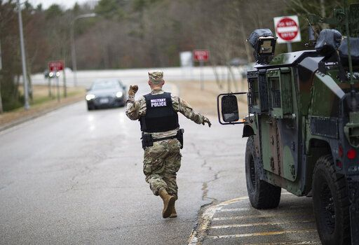 A member of the Rhode Island National Guard Military Police directs a motorist with New York license plates at a checkpoint on I-95 near the border with Connecticut where New Yorkers must pull over and provide contact information and are told to self-quarantine for two weeks, Saturday, March 28, 2020, in Hope Valley, R.I. Rhode Island Gov. Gina Raimondo on Saturday ordered anyone visiting the state to self-quarantine for 14 days and restricted residents to stay at home and nonessential retail businesses to close Monday until April 13 to help stop the spread of the coronavirus.