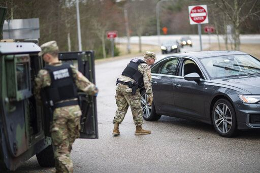 A member of the Rhode Island National Guard Military Police directs a motorist with New York license plates at a checkpoint on I-95 over the border with Connecticut where New Yorkers must pull over and provide contact information and are told to self-quarantine for two weeks, Saturday, March 28, 2020, in Hope Valley, R.I. Rhode Island Gov. Gina Raimondo on Saturday ordered anyone visiting the state to self-quarantine for 14 days and restricted residents to stay at home and nonessential retail businesses to close Monday until April 13 to help stop the spread of the coronavirus.