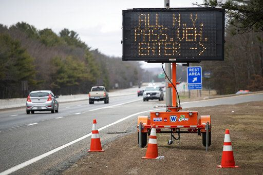 A sign instructs motorists with New York license plates to pull over at a checkpoint on I-95 over the border from Connecticut where New Yorkers must pull over and provide contact information and are told to self-quarantine for two weeks, Saturday, March 28, 2020, in Hope Valley, R.I. Rhode Island Gov. Gina Raimondo on Saturday ordered anyone visiting the state to self-quarantine for 14 days and restricted residents to stay at home and nonessential retail businesses to close Monday until April 13 to help stop the spread of the coronavirus.