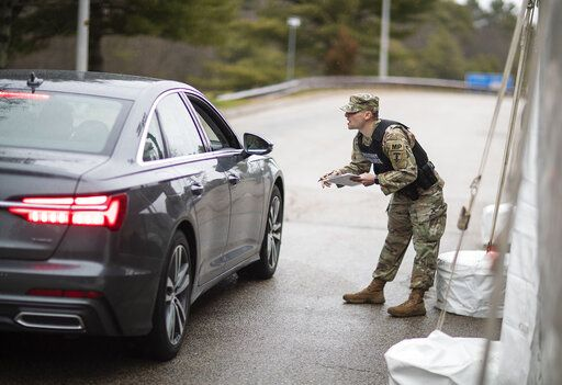 A member of the Rhode Island National Guard Military Police talks with a motorist with New York license plates at a checkpoint on I-95 near the border with Connecticut where New Yorkers must pull over and provide contact information and are told to self-quarantine for two weeks, Saturday, March 28, 2020, in Hope Valley, R.I. Rhode Island Gov. Gina Raimondo on Saturday ordered anyone visiting the state to self-quarantine for 14 days and restricted residents to stay at home and nonessential retail businesses to close Monday until April 13 to help stop the spread of the coronavirus.