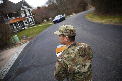 Rhode Island Air National Guard Tsgt. William Randall walks through the Watch Hill neighborhood looking for New York residents to inform them of self quarantine orders, Saturday, March 28, 2020, in Westerly, R.I. States are pulling back the welcome mat for travelers from the New York area, which is the epicenter of the country's coronavirus outbreak, and some say at least one state's measures are unconstitutional. Gov. Gina Raimondo ratcheted up the measures announcing she ordered the state National Guard to go door-to-door in coastal communities starting this weekend to find out whether any of the home's residents have recently arrived from New York and inform them of the quarantine order.