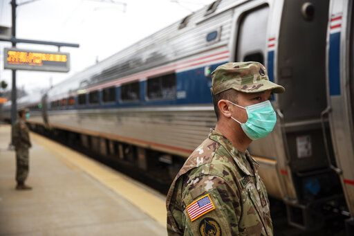 Members of the Rhode Island National Guard look for passengers getting off from a train from New York as it arrives Saturday, March 28, 2020, in Westerly, R.I. States are pulling back the welcome mat for travelers from the New York area, which is the epicenter of the country's coronavirus outbreak, and some say at least one state's measures are unconstitutional. Gov. Gina Raimondo ratcheted up the measures Friday afternoon, announcing she'll also order the state National Guard to go door-to-door in coastal communities starting this weekend to find out whether any of the home's residents have recently arrived from New York and inform them of the quarantine order.
