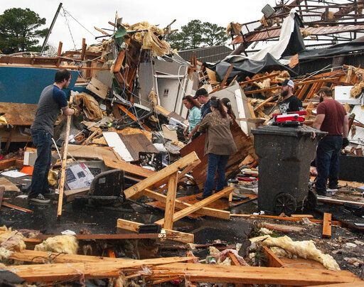 A group of people help clear debris and salvage items from Pawn Depot after a tornado touched down Saturday, March 28, 2020, in Jonesboro, Ark. (Quentin Winstine/The Jonesboro Sun via AP)