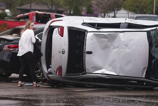 Meagen Matuszyk retrieves personal items from the trunk of her vehicle after it was turned on its side at The Mall at Turtle Creek in Jonesboro, Ark., Saturday, March 28, 2020, after a tornado touches down in the area. Matuszyk said she was in the Dillard's store in the mall when the tornado passed. (Quentin Winstine/The Jonesboro Sun via AP)