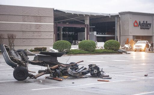 The damaged remains of a vehicle lie in a parking lot in front of a damaged Ashley Homestore after a tornado stuck Saturday, March 28, 2020, in Jonesboro, Ark. (Quentin Winstine/The Jonesboro Sun via AP)
