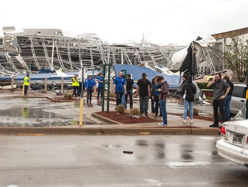 A group of people stand outside a damaged Best Buy after a tornado touched down Saturday, March 28, 2020, at The Mall at Turtle Creek in Jonesboro, Ark. (Quentin Winstine/The Jonesboro Sun via AP)