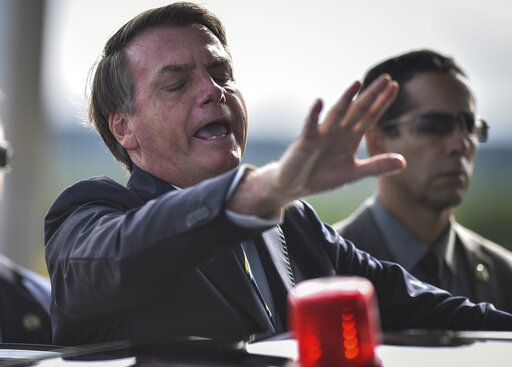 Brazil's President Jair Bolsonaro greets supporters and journalists as he arrives to give a news conference on the new coronavirus at Planalto presidential palace in Brasilia, Brazil, Friday, March 27, 2020. Even as coronavirus cases mount in Latin America's largest nation, Bolsonaro is calling the pandemic a momentary, minor problem and saying strong measures to contain it are unnecessary.