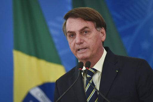 Brazil's President Jair Bolsonaro speaks to journalists about the new coronavirus at Planalto presidential palace in Brasilia, Brazil, Friday, March 27, 2020. Even as the new coronavirus cases mount in Latin America's largest nation, Bolsonaro is calling the pandemic a momentary, minor problem and saying strong measures to contain it are unnecessary.