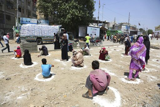 People sit at distance to receive relief goods during a nation-wide lockdown to contain outbreak of the coronavirus, in Karachi, Pakistan, Friday, March 27, 2020. The virus causes mild or moderate symptoms for most people, but for some, especially older adults and people with existing health problems, it can cause more severe illness or death.