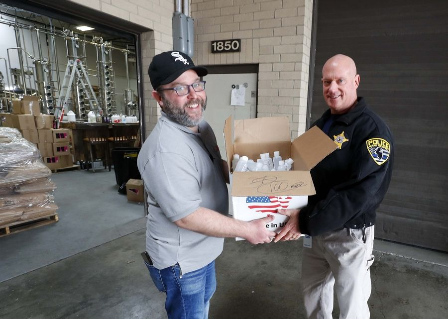 Aaron Johnson, Two Eagles Distillery business manager, hands a box of hand sanitizer to Mount Prospect Chief of Police John Koziol Saturday.