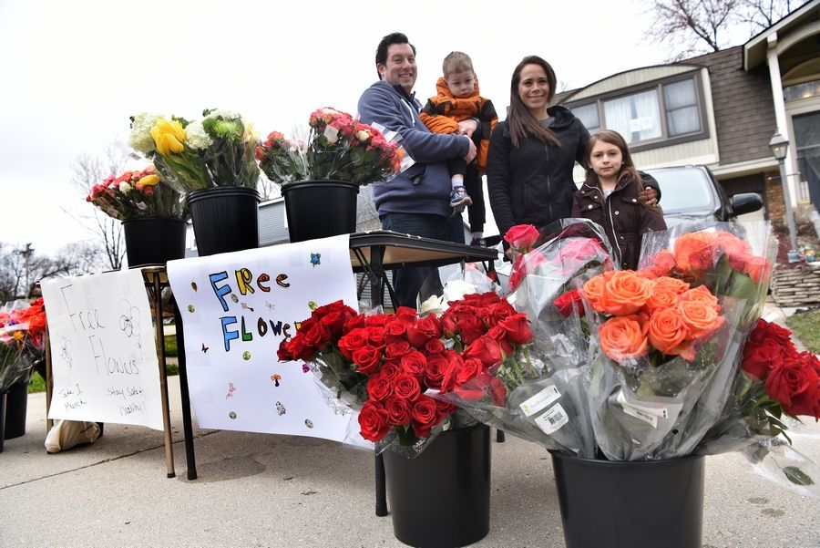"Krystal Glassman, her husband Danny and children Eden and Levi with a table full of flowers they set out Sunday for anyone who wants to stop by and pick them up. ""It's pretty amazing how this has caught on,"" Danny Glassman said."