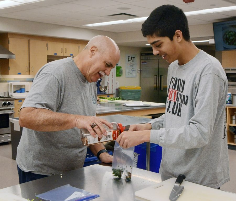 "Karl ""Van"" Dillenkoffer adds spice to his prepped food with the help of sophomore Aayush Dixit as Fittest Loser contestants take a cooking class with students from the Food Revolution Club at Stevenson High School in Lincolnshire recently."