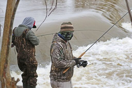 March 29, 2020 Fishing is still allowed under the stay at home order in Wisconsin. While the weather was windy and wet, and the water high, a group of fisherman on the Milwaukee River in Keltzsch Park in Glendale met a with some success fishing for steelhead or rainbow trout. Here fisherman on the bank fishing. Bandanas and balaclavas filled in for medical masks and kept the anglers warm as well. (Michael Sears/Milwaukee Journal-Sentinel via AP)