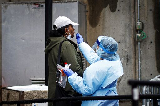A patient is given a COVID-19 test by a medical worker outside Brooklyn Hospital Center, Sunday, March 29, 2020, in Brooklyn borough of New York. The new coronavirus causes mild or moderate symptoms for most people, but for some, especially older adults and people with existing health problems, it can cause more severe illness or death.