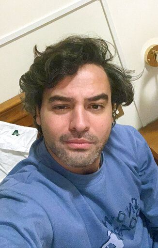 Andrea Napoli, 33, takes a selfie in a hotel being used for patients recovering from coronavirus, in Rome, Sunday, March 29, 2020. Andrea Napoli, a lawyer in Rome, developed a cough and fever less than a week after Italy's premier locked down the entire nation, including the capital which had continued life as usual while the virus raged in the north. He received a positive diagnosis for COVID-19 three days later. Initially, Napoli was told to quarantine at home with the warning that his condition could deteriorate suddenly, and it did. By the next day, he was hospitalized in intensive care, with X-rays confirming he had developed pneumonia. (Andrea Napoli via AP)