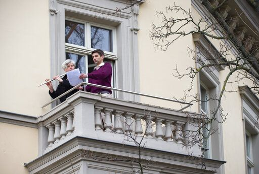 A flutist plays 'By loving forces silently surrounded...' by Dietrich Bonhoeffer on her balcony, as people practice social distancing due to coronavirus in Erfurt, central Germany, Sunday, March 29, 2020. For most people, the new coronavirus causes only mild or moderate symptoms, such as fever and cough. For some, especially older adults and people with existing health problems, it can cause more severe illness, including pneumonia.