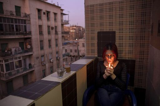 In this Oct. 28, 2019 photo, Egyptian transgender woman and activist Malak el-Kashif smokes a cigarette in the balcony of her apartment in Cairo, Egypt. She has been ostracized by her family and scorned by some who accuse her of tampering with God's creation. She has been attacked by others scandalized by her activism for LGBTQ rights. Legally, she still holds a male's identity card.