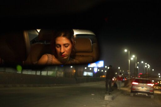 "In this Feb. 20, 2020 photo, transgender woman and activist Malak el-Kashif, reflected in the rear view mirror of a car, looks at her mobile phone, in Cairo, Egypt. Shortly before her birthday last year, el-Kashif posted a picture of herself online writing that she had completed her gender transitioning surgeries. One mother approached her at a hospital and said she sought medical help for her daughter after hearing el-Kashif's story. Another time, a transgender man stopped her to let her know that ""To me, you are resistance."""