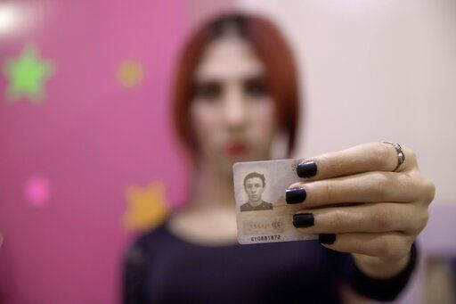 In this Oct. 28, 2019 photo, transgender woman Malak el-Kashif shows her identification card that has not been changed after her transition, in Cairo, Egypt. She has been ostracized by her family and scorned by some who accuse her of tampering with God's creation. She has been attacked by others scandalized by her activism for LGBTQ rights. Legally, she still holds a male's identity card.