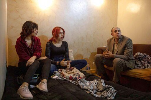 "In this Oct. 28, 2019 photo, activist and transgender woman Malak el-Kashif, center, sits with her lawyer and friend at her apartment in Cairo, Egypt. El-Kashif said she never received a response to her case. She was diagnosed with ""gender identity disorder,"" she said. The term was replaced in the American Psychiatric Association's diagnostic guide by ""gender dysphoria""-- a disconnect between assigned gender at birth and the one a person identifies with, which may lead to significant distress."
