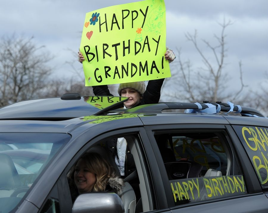Sophie Obrill, 11, of Arlington Heights holds a birthday sign for her great-grandmother, Mary Lett, who turned 90 Monday. Family members held a drive-by birthday party parade to celebrate the milestone.