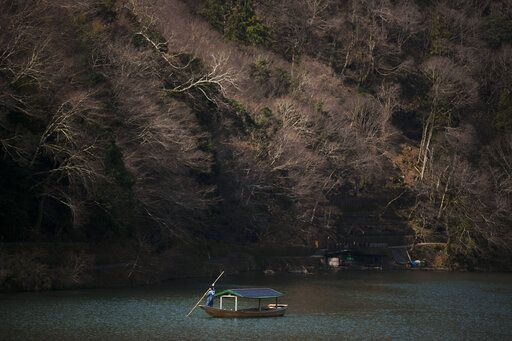 A boatman glides his boat across the river in the Arashiyama district of Kyoto, Japan, March 18, 2020. Widening travel restrictions and closures of most tourism and entertainment venues have gutted the tourism industry in many parts of the world, as well as in Japan.
