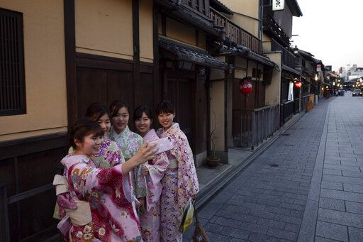 A group of Japanese women wearing kimono takes a selfie in the Gion district of Kyoto, Japan on March 18, 2020. Japanese tourism industry has taken a beating after Beijing banned group tours in late January.