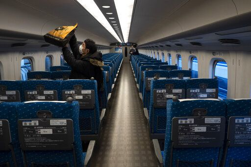 A traveler places his bag in an overhead luggage rack in a bullet train bound for Kyoto and Osaka at Tokyo Station in Tokyo, March 17, 2020.