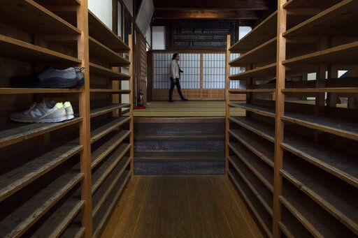 "A tourist walks past shoe racks provided for visitors at Tenryuji Temple in the Arashiyama district of Kyoto, Japan, March 18, 2020. ""Arashiyama is empty,"" is a new catchphrase that appeared on posters in the area. ""It's time to visit Kyoto,"" they say, because there are no long lines and waiting to do river rafting, get into popular temples or cross the bridge."