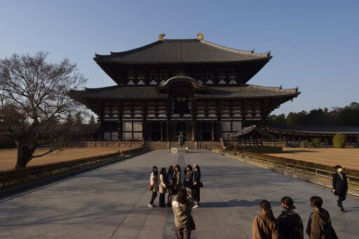 Tourists pause for photos in front of Todaiji temple's main hall in Nara, Japan, March 17, 2020. Nara was among the first Japanese town hit by the COVID-19 in late January, when a tour bus driver in town tested positive for the virus, becoming the first Japanese patient after carrying tourists from Wuhan, the epicenter of the pandemic.
