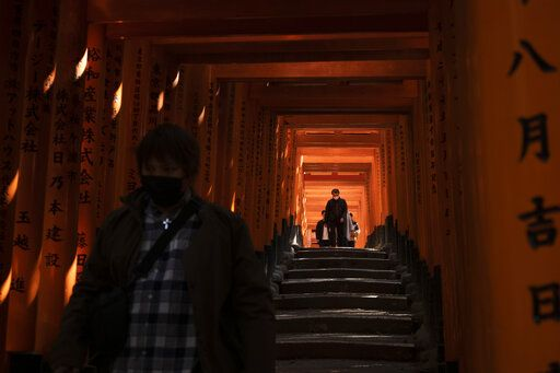 Tourists walk through torii gates at Fushimi Inari Shrine in Kyoto, Japan, March 18, 2020. Japanese tourism industry has taken a beating after Beijing banned group tours in late January.