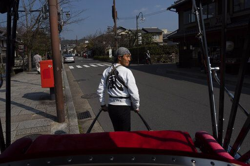 A rickshaw puller crosses the street in the Arashiyama district of Kyoto, Japan, March 18, 2020.