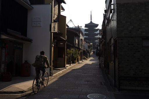 A man rides his bike toward Yasaka Pagoda in the Higashiyama district of Kyoto, Japan, March 19, 2020. Kyoto's city government has an emergency fund for small to medium-size businesses who suffered sharp sales decline since the coronavirus outbreak.