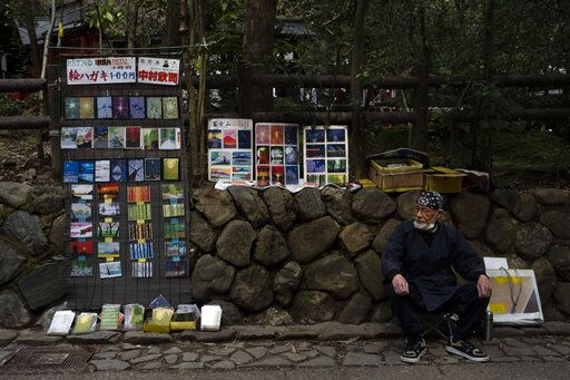 "Artist Kinji Kimura, 76, who sells postcard-sized prints of work, sits on a stool while waiting for customers near the Arashiyama Bamboo Forest in Kyoto, Japan, March 18, 2020. ""Arashiyama is empty,"" is a new catchphrase that appeared on posters in the area. ""It's time to visit Kyoto,"" they say, because there are no long lines and waiting to do river rafting, get into popular temples or cross the bridge."