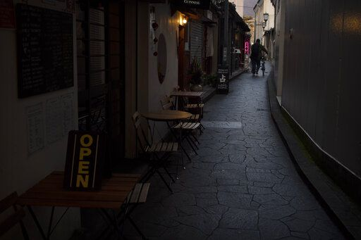 A man walks with his bike through a narrow alley lined with restaurants in Nara, Japan, Tuesday, March 17, 2020.