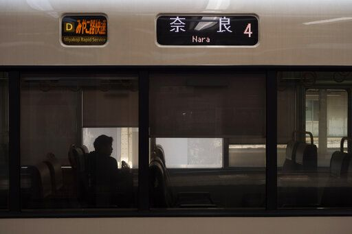 A man is silhouetted while sitting in a train bound for Nara at Kyoto Station in Kyoto, Japan on March 17, 2020.