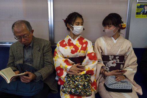 Two women wearing kimono chat in a train in Kyoto, Japan, March 18, 2020. Japanese tourism industry has taken a beating after Beijing banned group tours in late January. Japan's government restricted entry from China and South Korea in early March, then expanded the measures to parts of Europe.