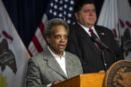 Illinois Gov. J.B. Pritzker, right, looks on as Mayor Lori Lightfoot speaks at the Thompson Center in Chicago during the daily update on the state's response to the coronavirus pandemic, Monday, March 30, 2020. (Ashlee Rezin Garcia/Sun-Times/Chicago Sun-Times via AP)